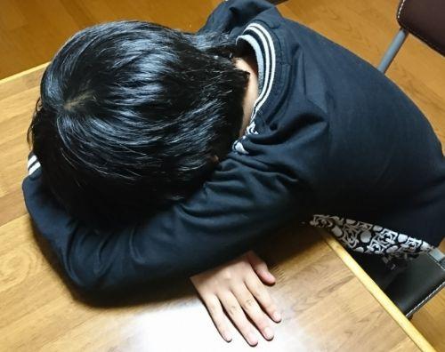 机にうつ伏せで寝る子